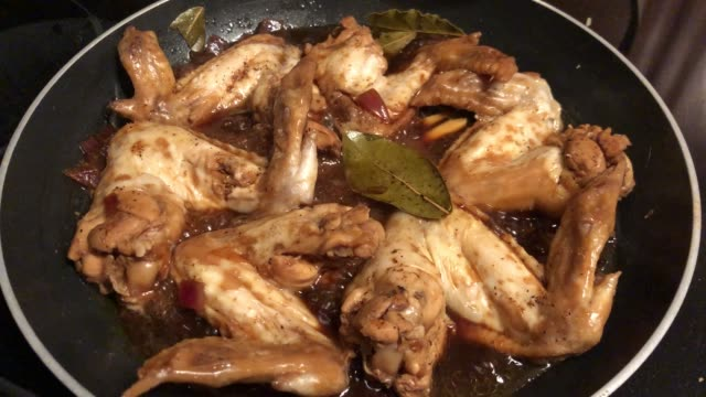 Hand-held shot of chicken wings frying in a pan, with sizzling sounds