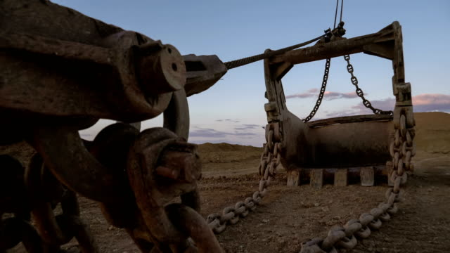 Handheld PAN shot of dragline excavator bucket 15 cubic meters with massive chains standing on the side of the quarry against sunset on the blue sky. video