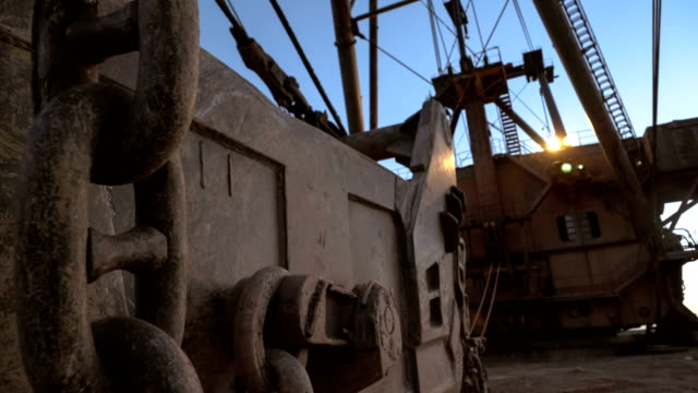 Handheld shot of dragline super heavy excavator with headlights on standing on the side of the quarry against sunset on the blue sky. video