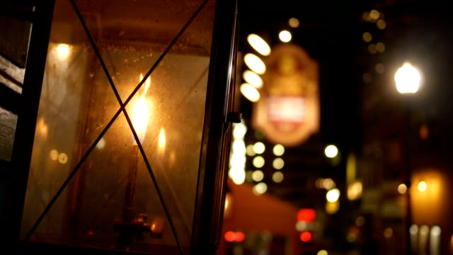Handheld shot of Lantern outside store window in urban downtown city at night video