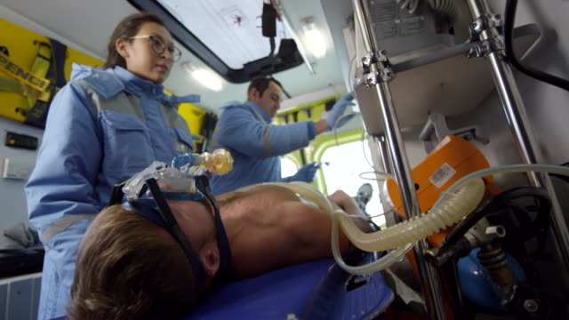 handheld shot of paramedics caring for patient in ambulance - first responders стоковые видео и кадры b-roll