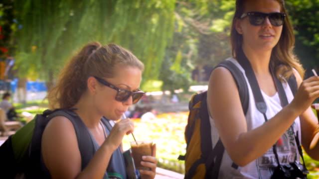 vídeos de stock, filmes e b-roll de tiro portátil de duas jovens andando e bebendo café gelado nas férias. - caminhada no gelo