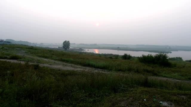 手持拍攝的攝影師在三腳架上的相機的位置。如畫的風景與河流、 樹木和具有令人難以置信的太陽的欄位。晨霧。 - 亞洲中部 個影片檔及 b 捲影像