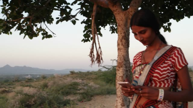 handheld shot of woman texts message share photo video smiles mobile phone communicates device connectivity signal wireless at sunset on hill outdoor nature hot summer magic hour beautiful low angle - sari filmów i materiałów b-roll