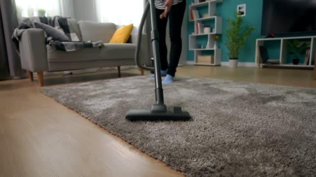 Handheld shot of young beautiful girl vacuuming carpet in her cozy living room video