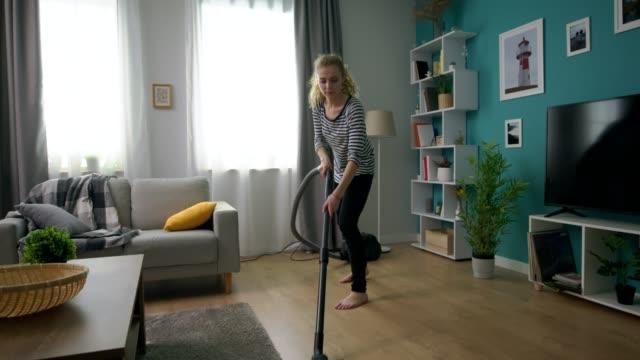 Handheld shot of young beautiful girl vacuuming her cozy apartment video