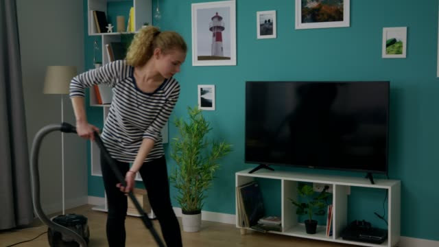 Handheld shot of young beautiful woman vacuuming her cozy apartment video