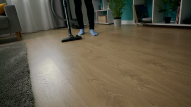 Handheld shot of young beautiful woman vacuuming her cozy living room video