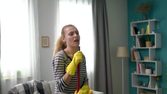 Handheld shot of young woman singing a song using a mop as a microphone video