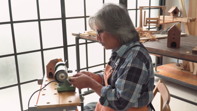 handheld side view: senior carpenter removing wood corners by electric machine in the workshop house