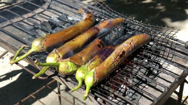 Handheld, side view shot of eggplants grilling over hot coals outdoors