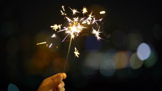 야간에 반짝이는 핸드헬드 스파클러 불꽃놀이 - new year 스톡 비디오 및 b-롤 화면
