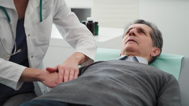 handheld-video-shows von arzt untersuchung magen eines älteren mannes. aufnahme mit roter heliumkamera in 8k - menschlicher verdauungstrakt stock-videos und b-roll-filmmaterial