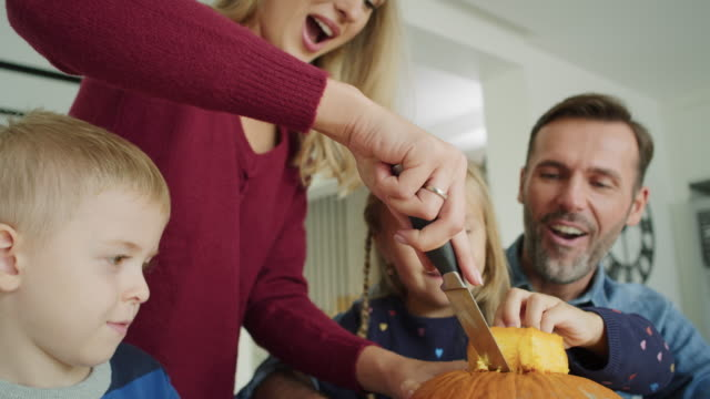 handheld video shows of family drilling pumpkins for halloween - incisione oggetto creato dall'uomo video stock e b–roll