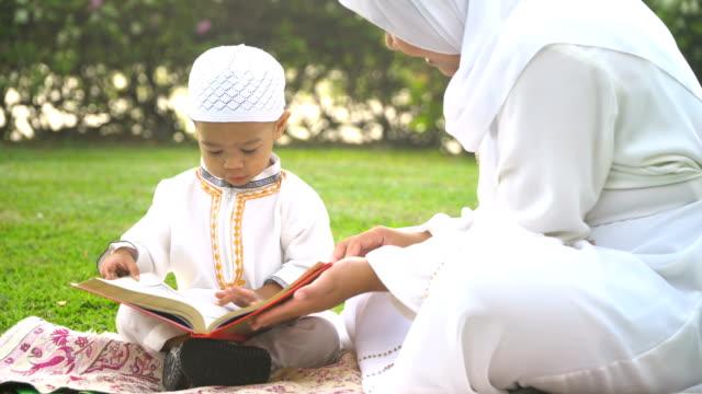 vídeos y material grabado en eventos de stock de ver mano: madre musulmana enseñar a su hijo a leer el corán en parque público - eid mubarak