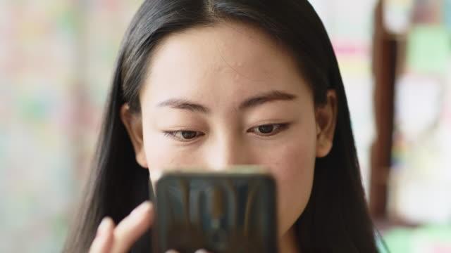 портативный взгляд вьетнамской женщины, глядя на смартфон - поколение z стоковые видео и кадры b-roll