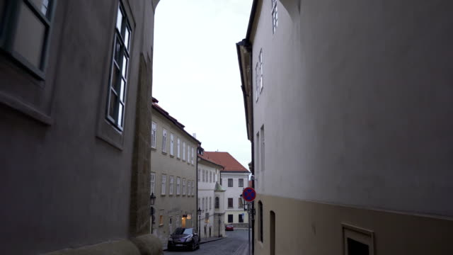 handheld view: walking out from small gate between tall building in local street in Prague