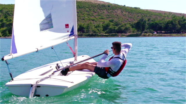 HD Handheld:Shot of Young Boats-man Sailing on Laser Class Boat HD 1080p: Handheld shot of young boats-man sailing on laser class boat using main sail, Adriatic sea, Europe recreational boat stock videos & royalty-free footage