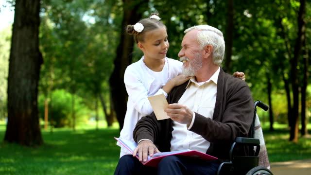 nonno handicappato che mostra alla nipote foto di famiglia che raccontano della nonna - nipote femmina video stock e b–roll