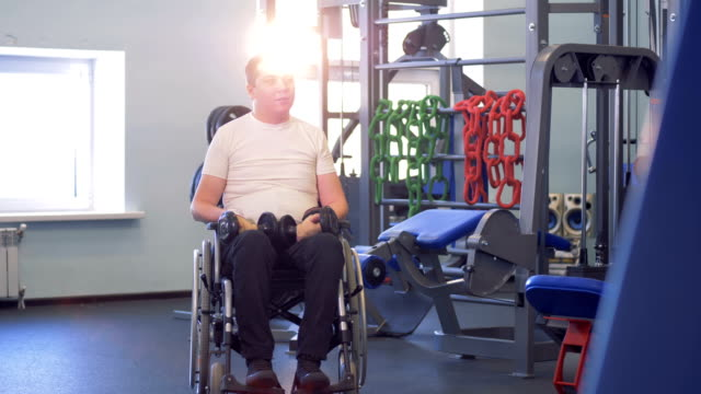 A handicapped man in a wheelchair is sitting in the middle of a gym, talking and smiling video