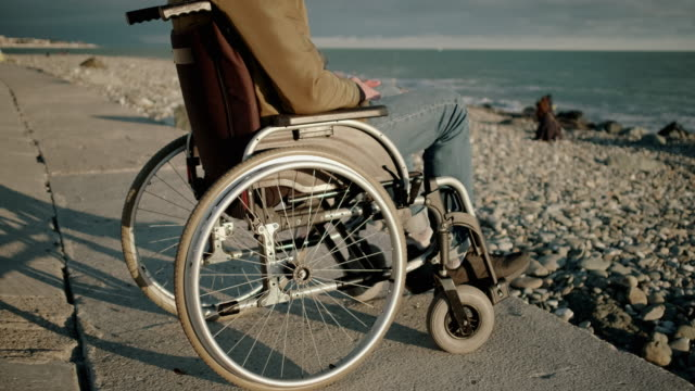 Handicapped man in wheelchair is alone with sea - vídeo