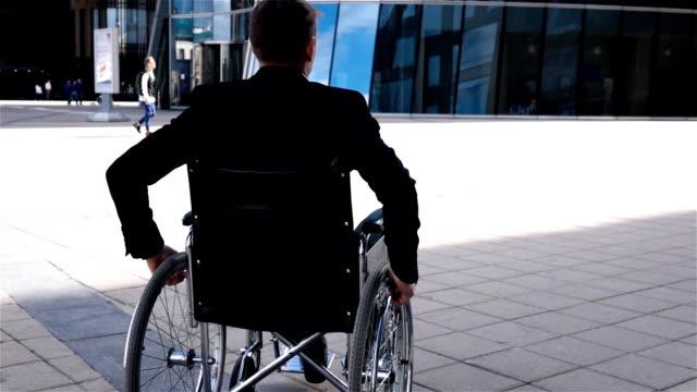 vídeos y material grabado en eventos de stock de hombre con discapacidad en silla de ruedas moverse cerca de moderno centro de negocios - deportes en silla de ruedas