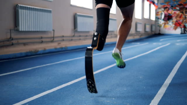 Handicapped person running on a track, back view.