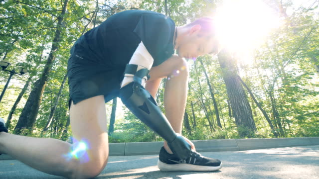 Handicapped person tying his shoes on a sun background, close up. A person ties his sneakers, using a bionic hand. prosthetic equipment stock videos & royalty-free footage