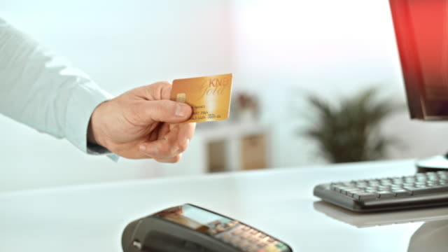 Handing out the credit card to the salesperson Medium shot of a man giving his credit card to the salesperson. gold card stock videos & royalty-free footage