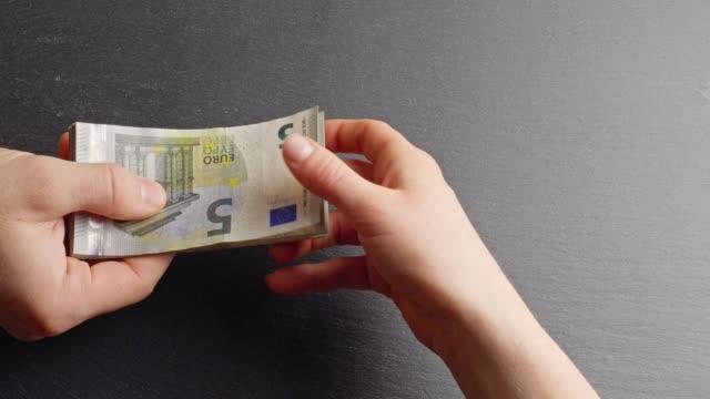 Handing over Five-Euro-banknotes