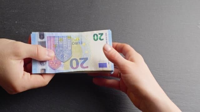 Handing over Twenty-Euro-banknotes Concept shot of two hands exchanging money. european union currency stock videos & royalty-free footage