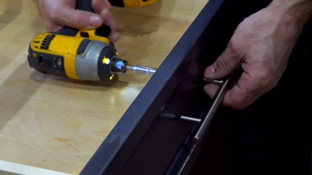 Handle installation of door handles on opening cabinet door in kitchen with a screwdriver