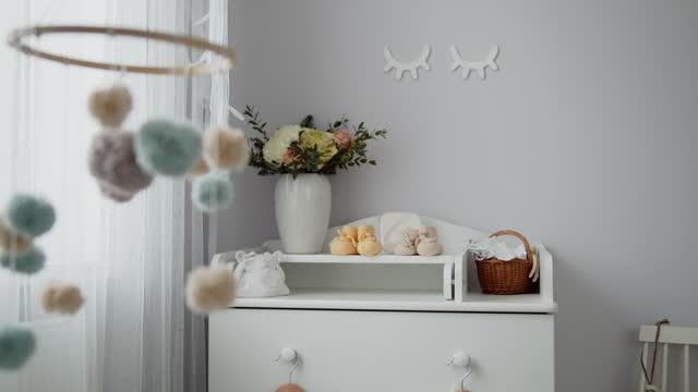 vídeos de stock, filmes e b-roll de móvel de bebê artesanal pendurado girando acima do berço no quarto da criança - mobile