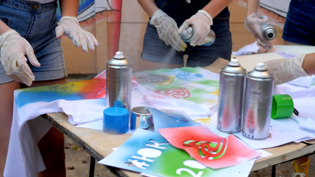 handmade, close-up hands with aerosol paint in slow motion, street painting, girls with spray paint into arms, girls on open air