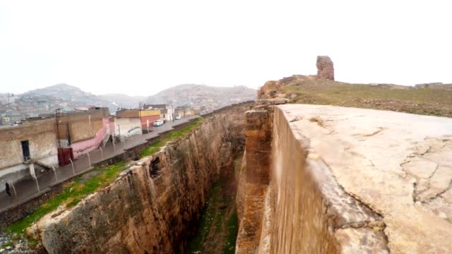 Hand-made Ditch of Urfa Castle Divides Ruins and Slum  Bird Flies in Pit Snow and Rain Put on Camera video
