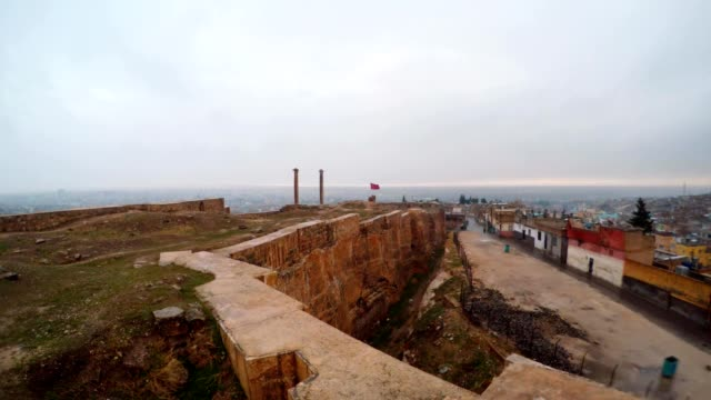 Hand-made Ditch of Urfa Castle Divides Ruins and Slum Far Two Columns Snow and Rain video