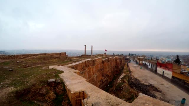 Hand-made Ditch of Urfa Castle Divides Ruins and Slum Far Two Columns Bird Flies Snow and Rain video