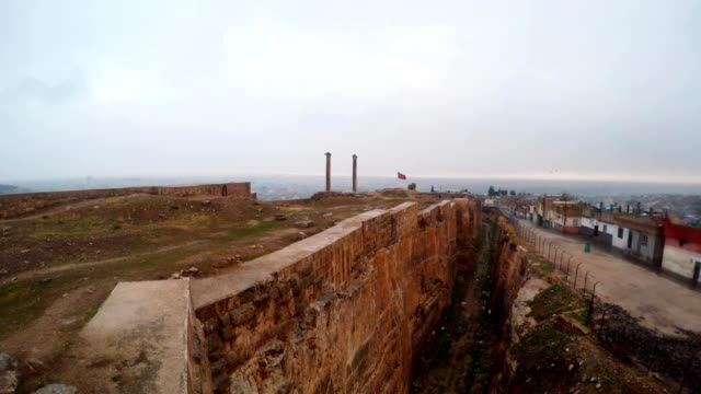 Hand-made Ditch of Urfa Castle Divides Ruins and Slum Far Two Columns Birds Fly Snow and Rain video