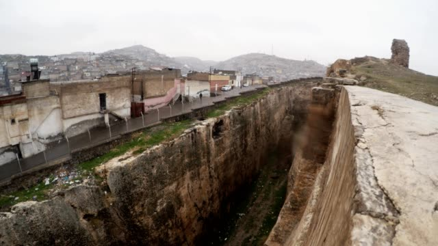Hand-made Ditch of Urfa Castle Divides Ruins and Slum Snow and Rain video