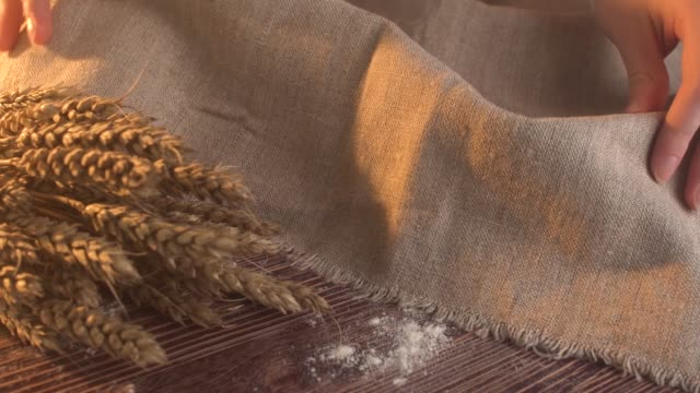 vídeos y material grabado en eventos de stock de hecho a mano pan sabroso acostado de arpillera en la mesa de madera con espigas de trigo, el trigo y la harina - cuchillo cubertería