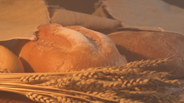 handmade tasty bread lying on burlap on the wooden table with flour, wheat and ears of wheat video