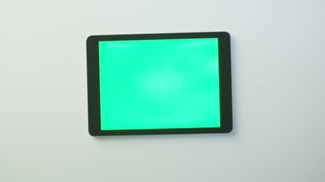 Hands are Putting Tablet PC with Green Screen on the White Table and Starting to Use it. Great for Mock-up Usage. video