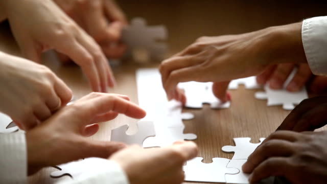 hands assembling jigsaw puzzle, help support in teamwork concept, closeup - puzzle video stock e b–roll