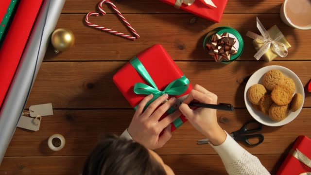 hands attaching name tag to christmas gift