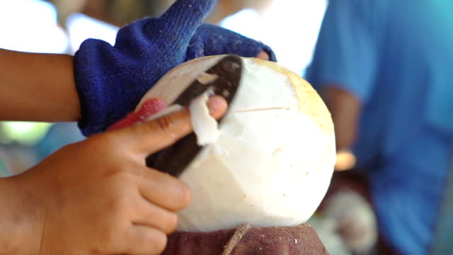 Hands chopping coconut with a knife Video of Hands chopping coconut with a knife. 4K(UHD) 3840x2160 format. coconut palm tree stock videos & royalty-free footage