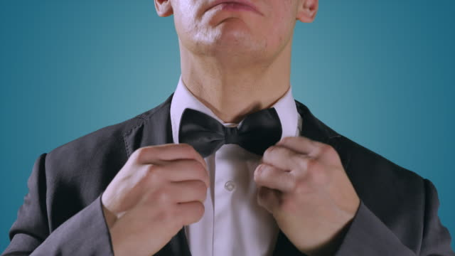Hands Close Up, Man in Black Suit Tuxedo, Turquoise Blue Background video