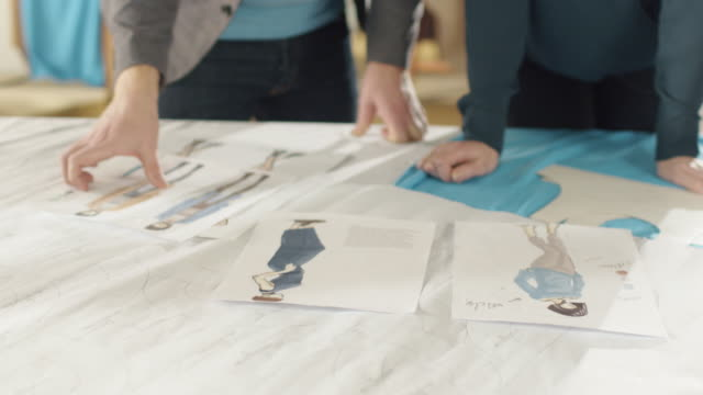 Hands Close-up of a Female and Male Fashion Designer Choosing Sketches for Their New Clothing Collection. Studio is Sunny. Sketches and Fabrics Lay on the Table, in the Background Colourful Fabrics are Visible. video
