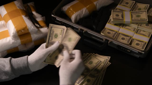 hands counting money with packs of narcotic drugs and money in the background - narcotico video stock e b–roll