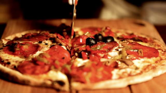 vídeos y material grabado en eventos de stock de las manos cortan la pizza en rodajas. vista de cerca de una deliciosa pizza antes de que se sirve a los clientes. - cortar en trozos preparar comida