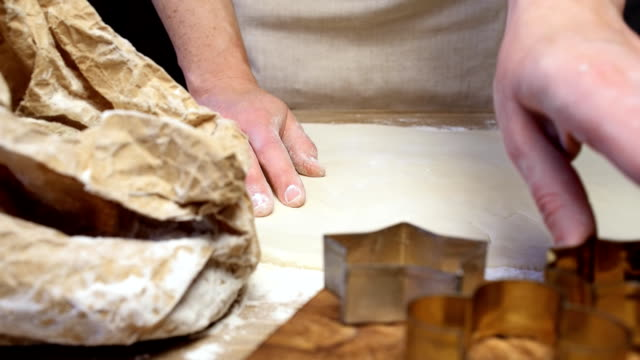 Hands cutting cookies Female hands cutting cookies from pastry dough on wooden table. Dolly shot. Slow motion cookie cutter stock videos & royalty-free footage